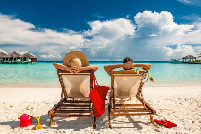 couple-in-loungers-on-beach-at-maldives